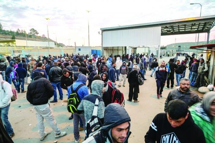 פועלים פלסטינים במחסום // צילום: אלכס ליבק, 'הארץ'